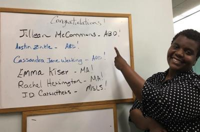 A photo of Jillean McCommons discussing a topic in front of a white board.